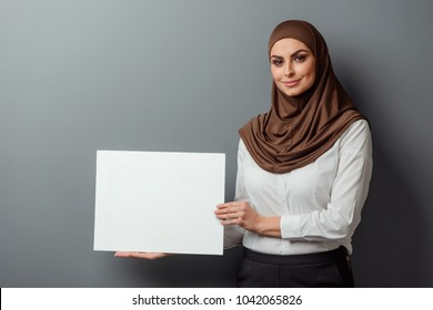 Muslim teacher showing an empty cardboard. Cheerful woman dressed in formal clothing and hijab.