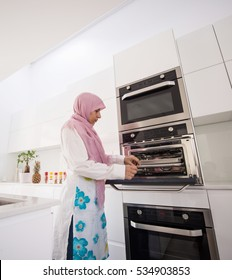 Muslim traditional clothing woman in white modern kitchen