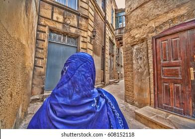 Muslim traditional woman visiting old historical city in Baku Azerbaijan. Innrer city Toned