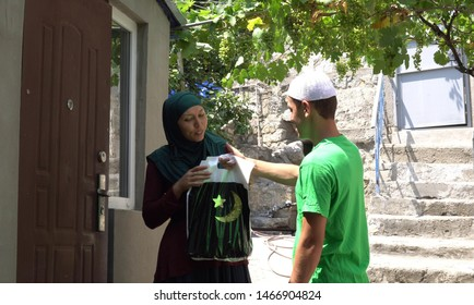 Muslim volunteer distributing charity giving and donated food packages. Holy month of Ramadan
