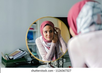 A Muslim woman adjusts her tudong (hijab head scarf) as she looks at herself into a round mirror in her home. Her headscarf is red orange and she is slim and attractive.