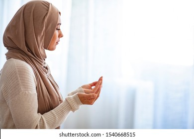 Muslim woman in beige hijab and traditional clothes praying for Allah, copy space. Muslim woman with hijab praying indoor at bright window. Young Muslim woman Praying