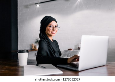 Muslim woman in a black hijab with a beautiful straight smile sitting at a table in a cafe working on a laptop