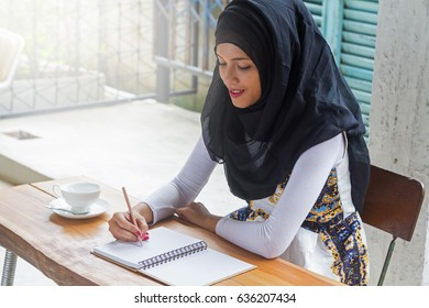 muslim woman in black hijab writing on note book on wood table in home.