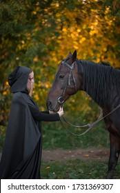 a Muslim woman in a burqa and a horse