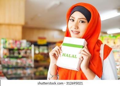 muslim woman buying halal food in a supermarket