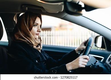 Muslim woman in car as driver. Arabic woman in hijab driving a car