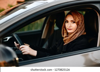 Muslim woman in car as driver. Arabic woman in hijab driving a car