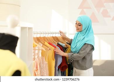 Muslim woman choosing clothes in modern shop