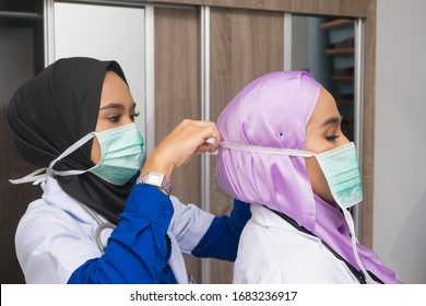 Muslim woman doctor helping her colleague wearing a surgical mask. Frontliner and preparation of personal protective equipment of medical staff.
