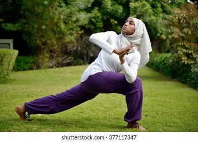 Muslim Woman doing yoga by the poolside in Dubai