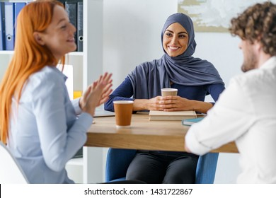 Muslim woman enjoys spending time with her coworkers. Good gathering during a coffee break. Social inclusion concept.