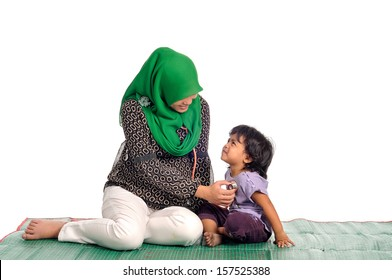 Muslim woman examining her little daughter, isolate on white