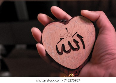 "Muslim woman hand holding heart(Love) shaped tag written in Arabic ""Allah"" English meaning of God."