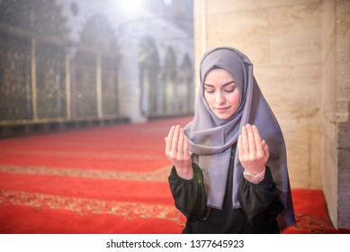 Muslim woman in headscarf and hijab prays with her hands up in air in mosque.Religion praying concept.Light beams comes from left.