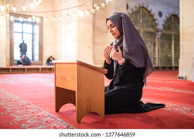 Muslim woman in headscarf and hijab prays with her hands up in air with Quran(holy book of Islam)in mosque.Religion praying concept.