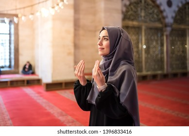 Muslim woman in headscarf and hijab prays with her hands up in air in mosque.Religion praying concept.