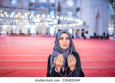 Muslim woman in headscarf and hijab prays with her hands up in air while holding rosary and looking up in mosque.Religion praying concept.