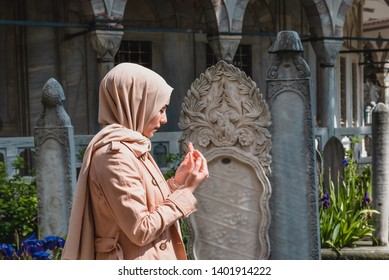 Muslim woman in headscarf and hijab prays with her hands up at an ancient cemetery.Religion praying concept.