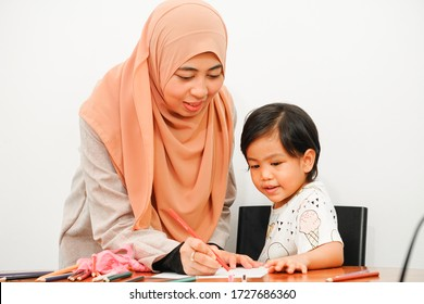 Muslim woman with her cute girl daughter learning and playing together at home. Home school education, parents teaching kids at home. Happy family. Mother and daughter