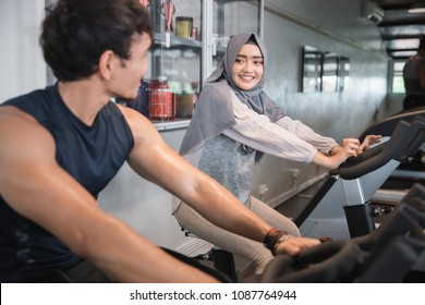 Muslim woman hijab and friend at the gym doing cardio exercises on static bike