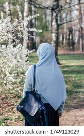 Muslim woman in hijab in a park next to a blossoming tree. Blue shawl and blue backpack. Modern muslim woman. Spring. Islamic woman. Education in Islam. Muslim student