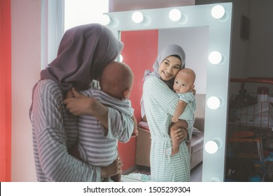 muslim woman with hijab playing with her baby looking at the mirror