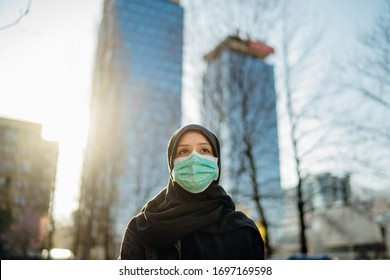 Muslim woman with hijab wearing protective surgical mask.Coronavirus COVID-19 pandemic lifestyle in Islamic country culture.Religion of Islam.Spiritual praying concerned person.Faith and hope