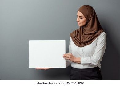 Muslim woman holding a blank card. Empty space for your text or picture, presentation mockup.