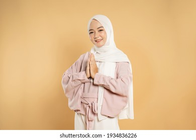muslim woman looking at camera showing hand together gesture