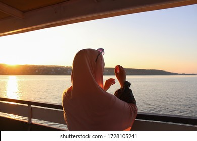 Muslim woman looks at the sea at sunset from the ship