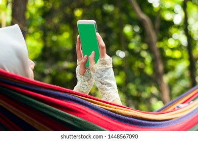 Muslim Woman lying at hammock with green screen cell phone