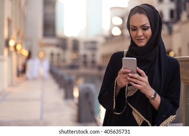 Muslim woman messaging on a mobile phone in the city.
