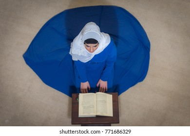 Muslim woman in a mosque reading the Quran