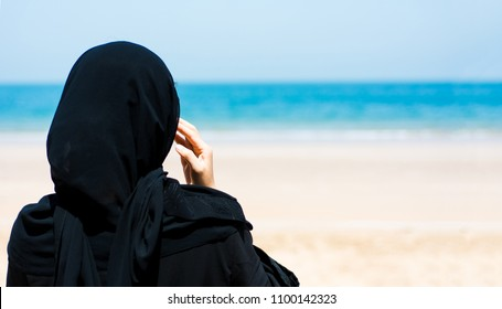 Muslim woman on the sunny beach back view