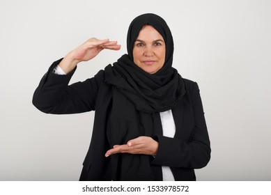 Muslim woman over isolated background gesturing with hands showing big and large size sign, measure symbol. Smiling looking at the camera. Measuring concept.