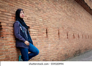 Muslim woman post on brick wall