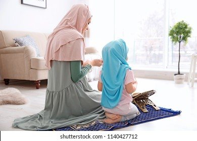 Muslim woman praying with her daughter at home
