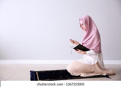 Muslim woman praying near light wall