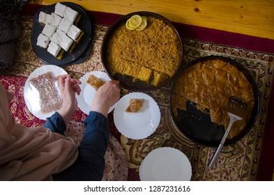 Muslim woman preparing food, cakes baklava and kadaif  for Eid