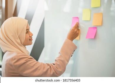 Mujer musulmana publicando la nota de los stickers. idea de lluvia de ideas y creatividad.
