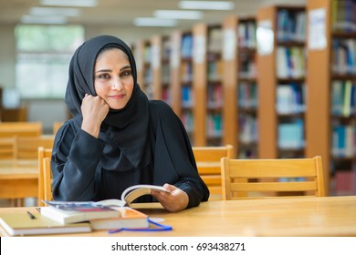 Muslim woman reading book at the library.