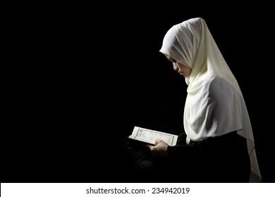 Muslim Woman Reading Quran on Black Background