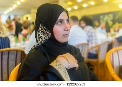 Muslim woman at restaurant waiting for food