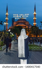 "Muslim woman with scarf in front of Blue Mosque (turkish: Sultanahmet camii). Lettering on mahya said: ""Welcome to the sultan of eleven months"".  Istanbul during Ramadan (aka Ramazan) month."