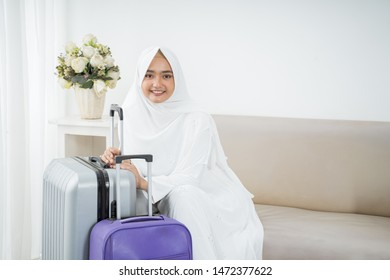 muslim woman sit wearing white traditional clothes for Ihram before umrah with suitcase