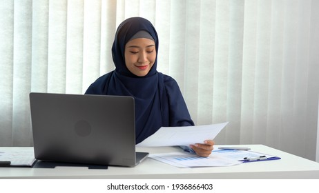 Muslim woman sitting happily at the office.