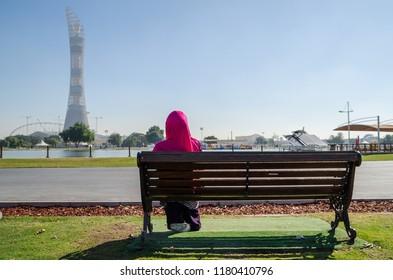 Muslim woman sitting on the bench in Aspire Park Doha, Qatar