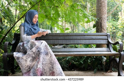 Muslim Woman  sitting on the chair and holding mobile phone.