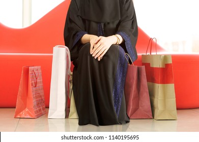 A muslim woman sitting with shopping bags at a mall in Saudi Arabia Gulf Middle East